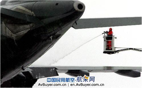机场的地勤人员在飞机起飞前向机翼喷撒除冰剂