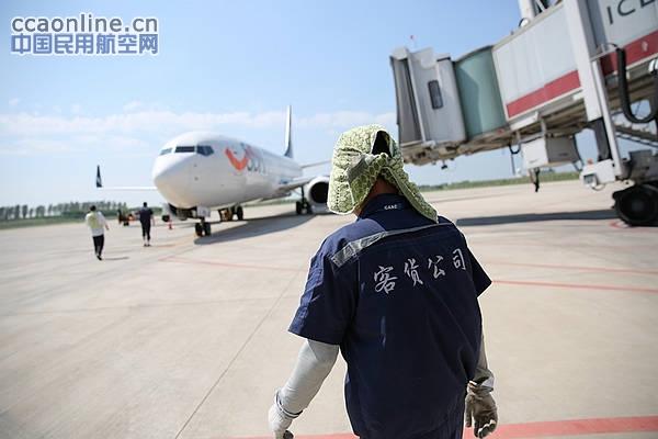 飞机刚落地,货运人员着手装卸货物 摄影:方明阳